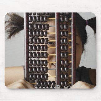 Young woman peering through abacus. mouse pad
