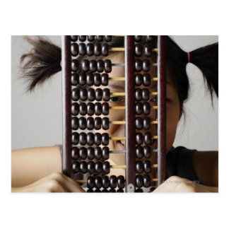Young woman peering through abacus. postcard