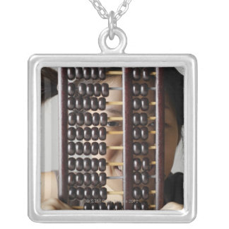 Young woman peering through abacus. silver plated necklace