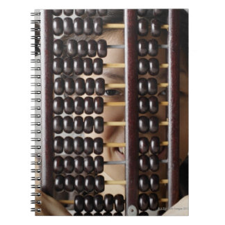 Young woman peering through abacus. spiral notebook