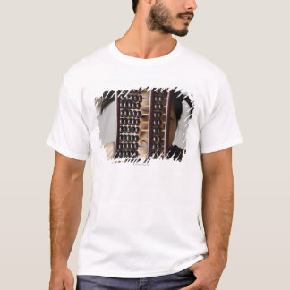 Young woman peering through abacus. T-Shirt