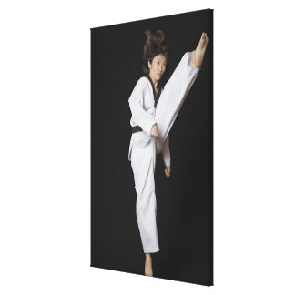 Young woman performing front kick canvas print