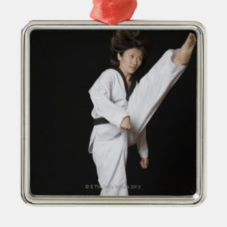 Young woman performing front kick christmas tree ornaments