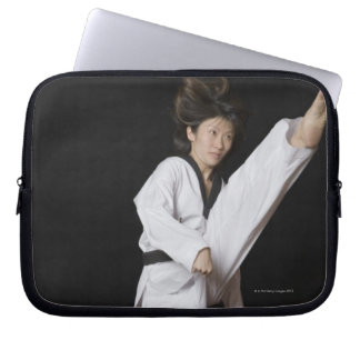 Young woman performing front kick laptop sleeve