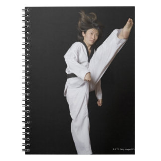 Young woman performing front kick notebooks
