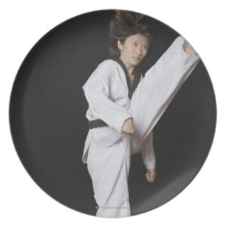 Young woman performing front kick plate