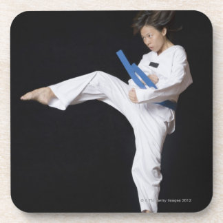 Young woman performing round kick coaster