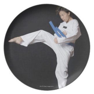 Young woman performing round kick plate
