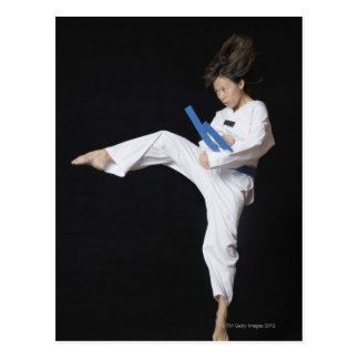 Young woman performing round kick postcard