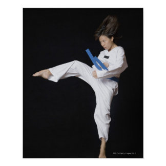Young woman performing round kick poster