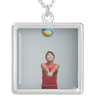 Young woman playing with volleyball silver plated necklace