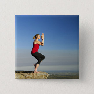 young woman practices yoga on a bluff in the 15 cm square badge