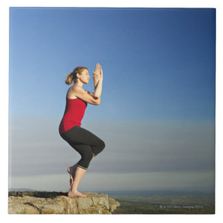young woman practices yoga on a bluff in the large square tile