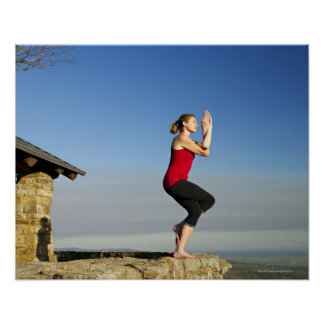 young woman practices yoga on a bluff in the poster