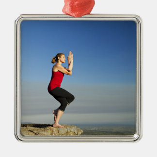 young woman practices yoga on a bluff in the Silver-Colored square decoration