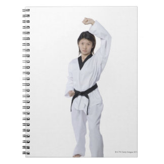 Young woman practicing upper block spiral notebook
