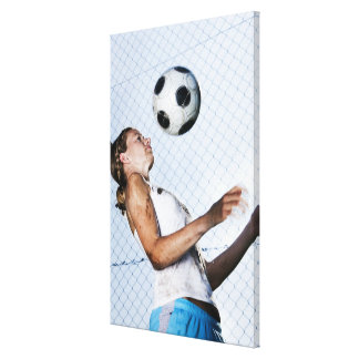 young woman practising with football canvas print