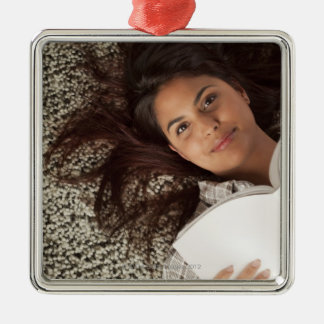 Young woman reading a book lying down christmas ornament