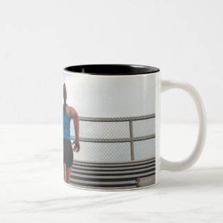 young woman running up steps Two-Tone coffee mug