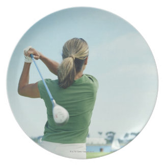Young woman swinging golf club, rear view plate