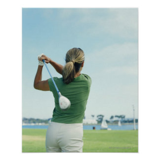 Young woman swinging golf club rear view poster