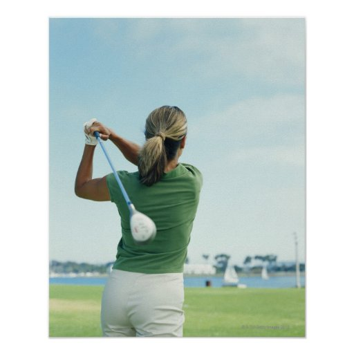 Young woman swinging golf club, rear view poster