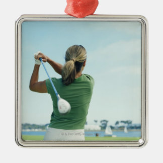 Young woman swinging golf club, rear view Silver-Colored square decoration
