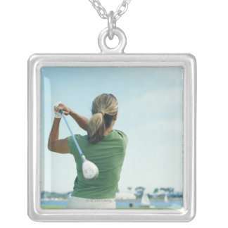 Young woman swinging golf club, rear view silver plated necklace
