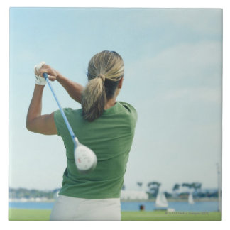 Young woman swinging golf club, rear view tile