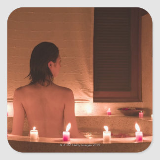Young woman taking bath with flower petals square sticker