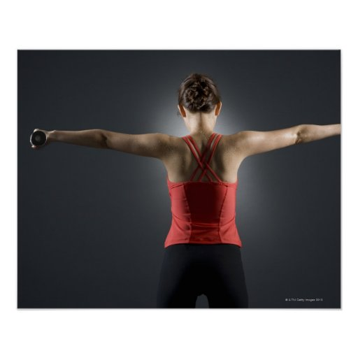 Young woman using dumbbells, rear view, studio poster