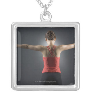 Young woman using dumbbells, rear view, studio square pendant necklace