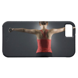 Young woman using dumbbells, rear view, studio tough iPhone 5 case
