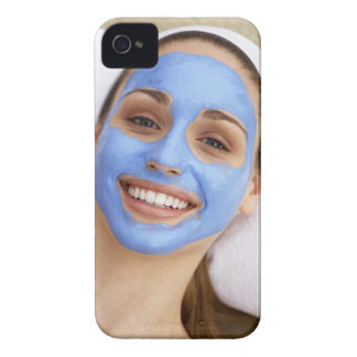 Young woman wearing facial mask, smiling, iPhone 4 case