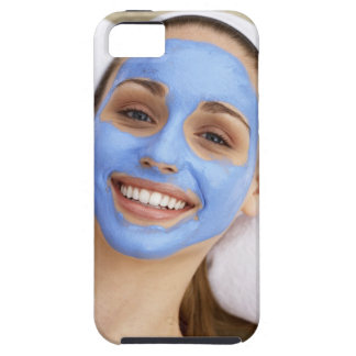 Young woman wearing facial mask, smiling, iPhone 5 cover