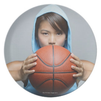 Young woman with basketball looking at camera plate
