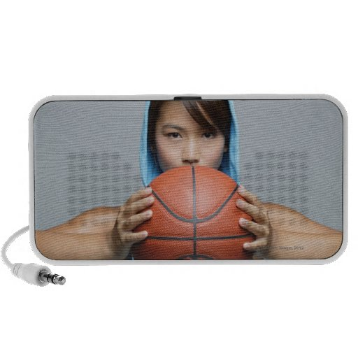 Young woman with basketball looking at camera portable speaker