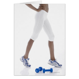 Young woman with dumbbells stretching (low card