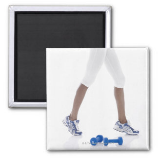 Young woman with dumbbells stretching (low magnets