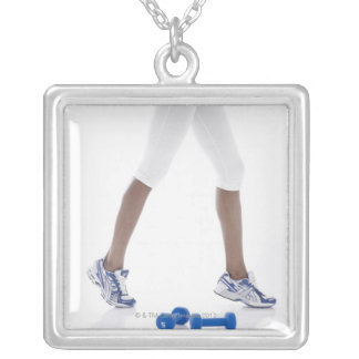 Young woman with dumbbells stretching (low square pendant necklace